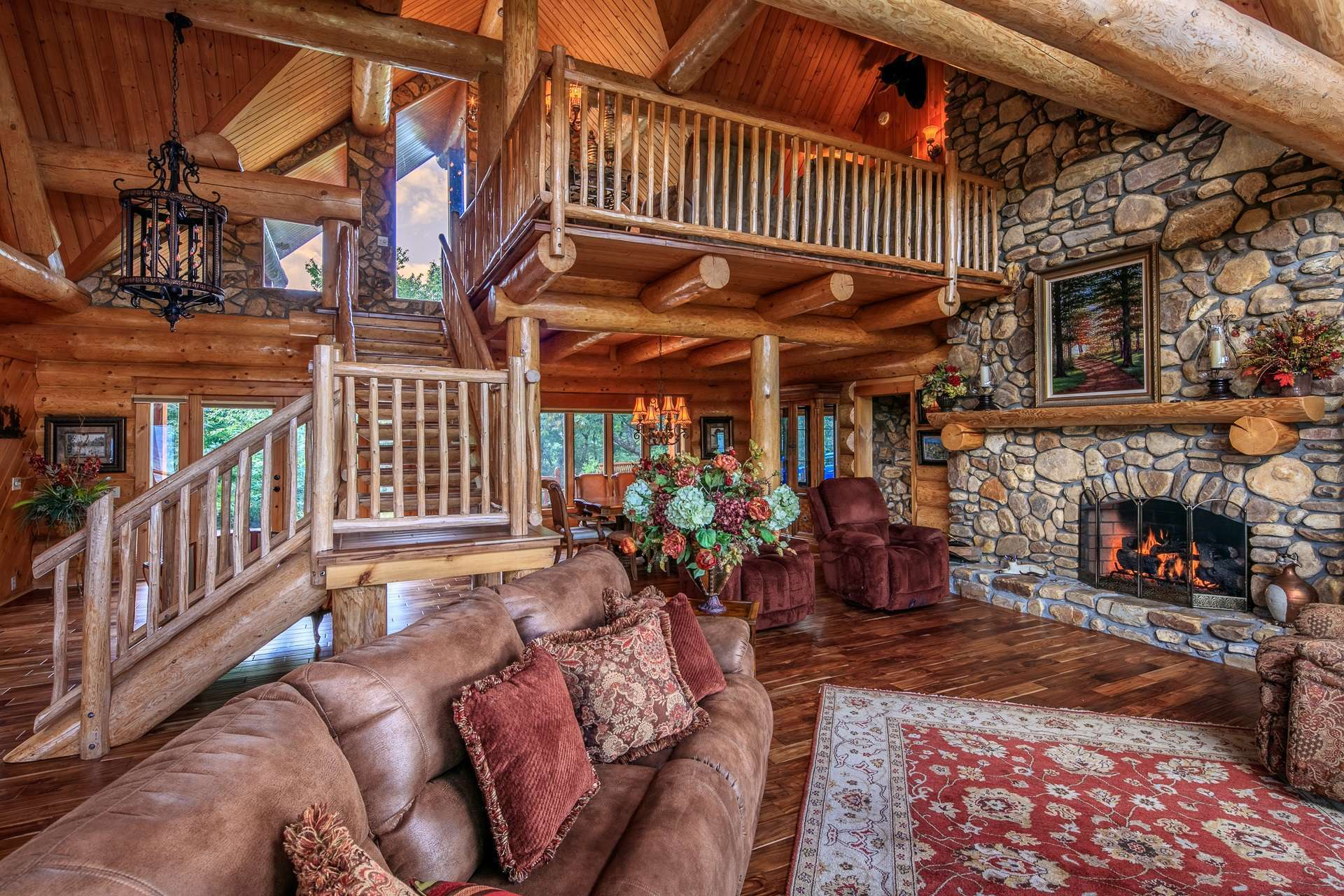 The captivating vaulted great room is designed to embrace both rustic and elegant details with the focus on the massive 2-story stone fireplace and the tremendous views.