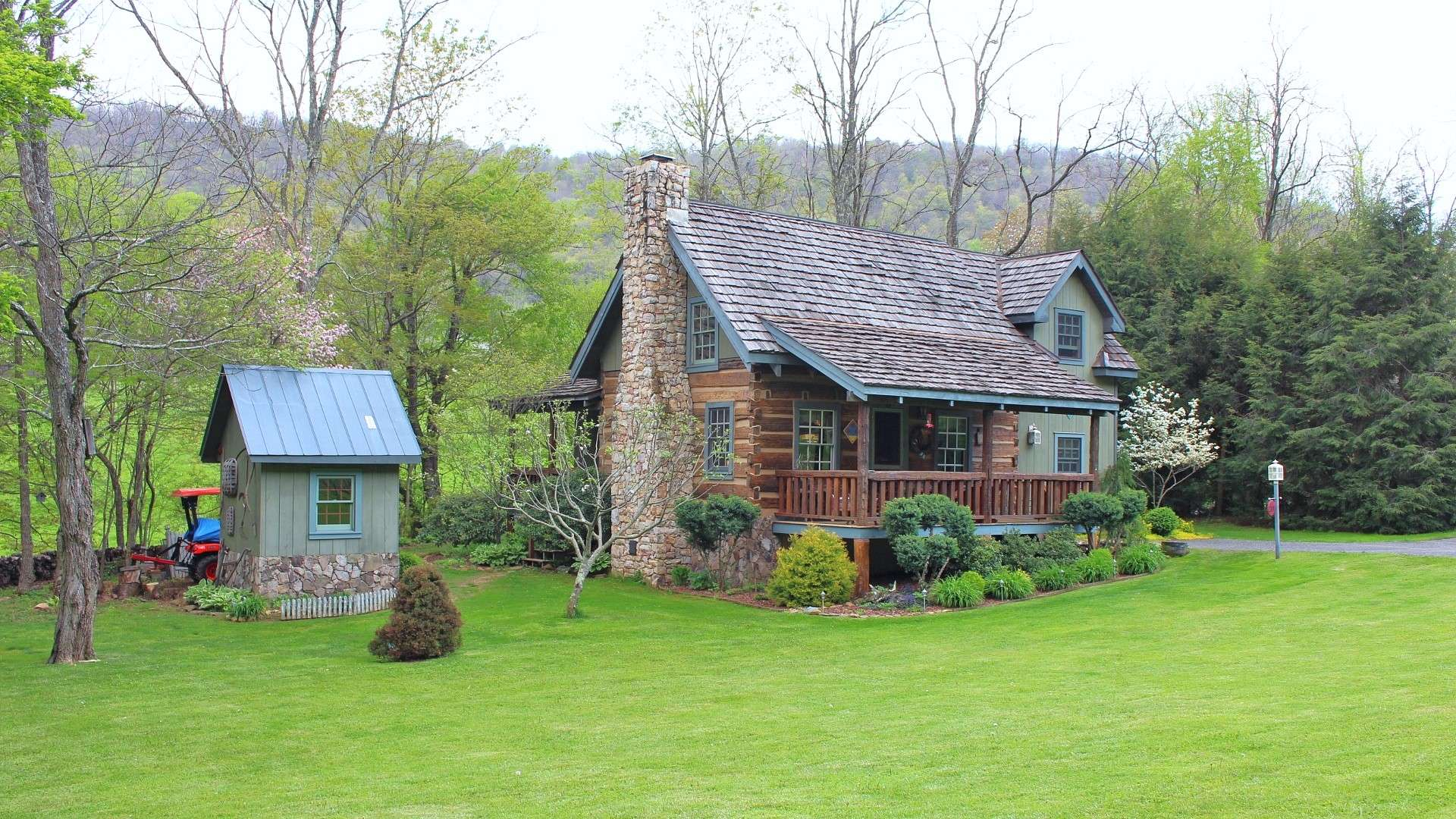 Offered at $279,900, this rustic 2-bedroom, 2-bath log cabin with wood floors, stone fireplace, many custom features, covered front and side porch, beautifully landscaped setting with fenced garden area, craftsman style outbuilding/workshop, another outbuilding and located in Chestnut Creek, just a short drive to West Jefferson, is perfect for your NC High Country retreat or full time home.