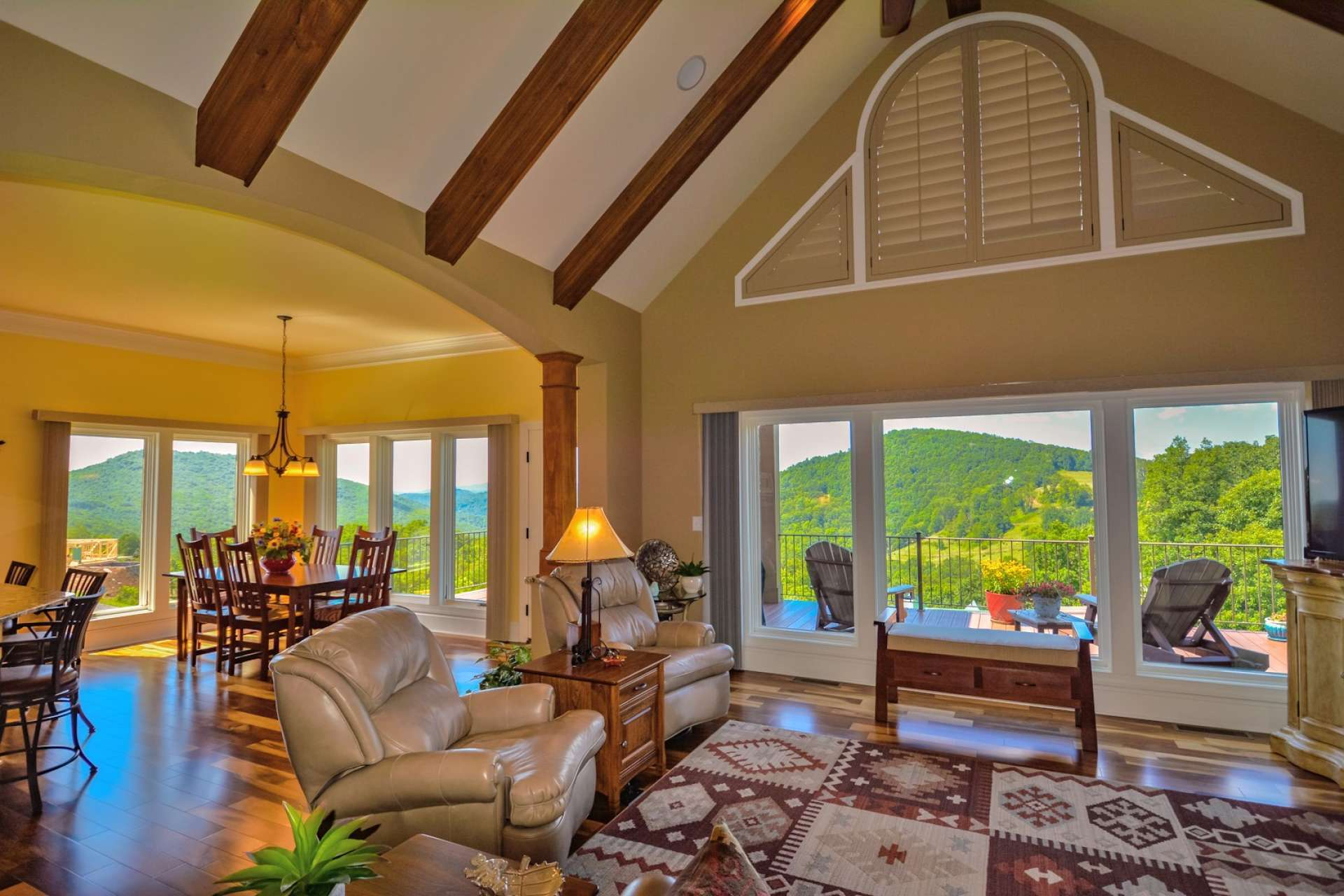 As you enter the home you'll step into an expansive great-room with vaulted cathedral ceiling with exposed beams and large rock fireplace with gas logs for ambiance and convenience. Extra wide windows frame the dramatic view beyond.