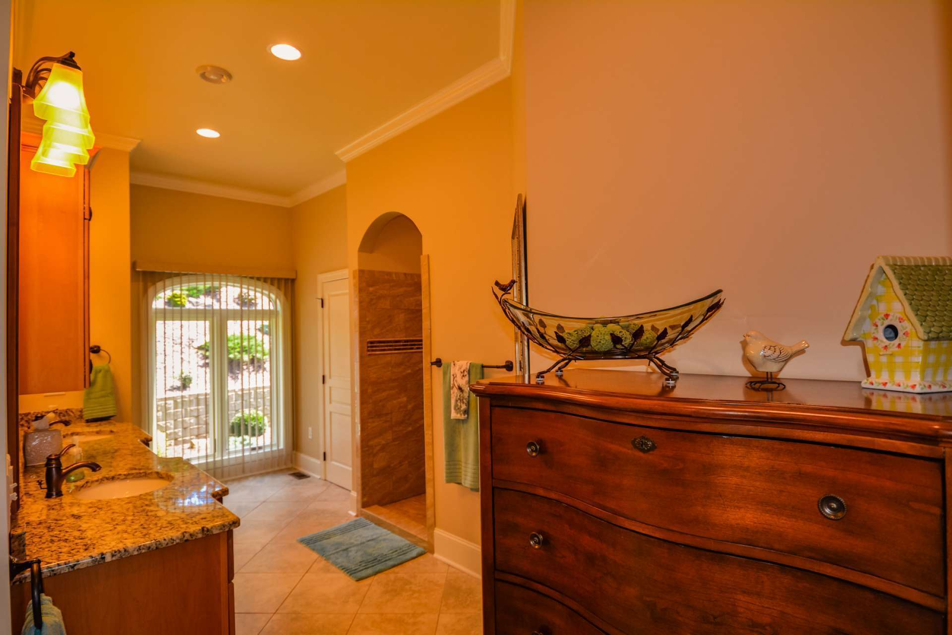 The gorgeous luxury master bath has a granite double vanity and a big window for natural light. An enormous walk-in shower welcomes you through an arched entryway. The shower includes separate handheld showerheads with diverters. Even the home's elongated, high-profile toilets are upgraded with soft close seats. The cabinetry is custom knotty alder.