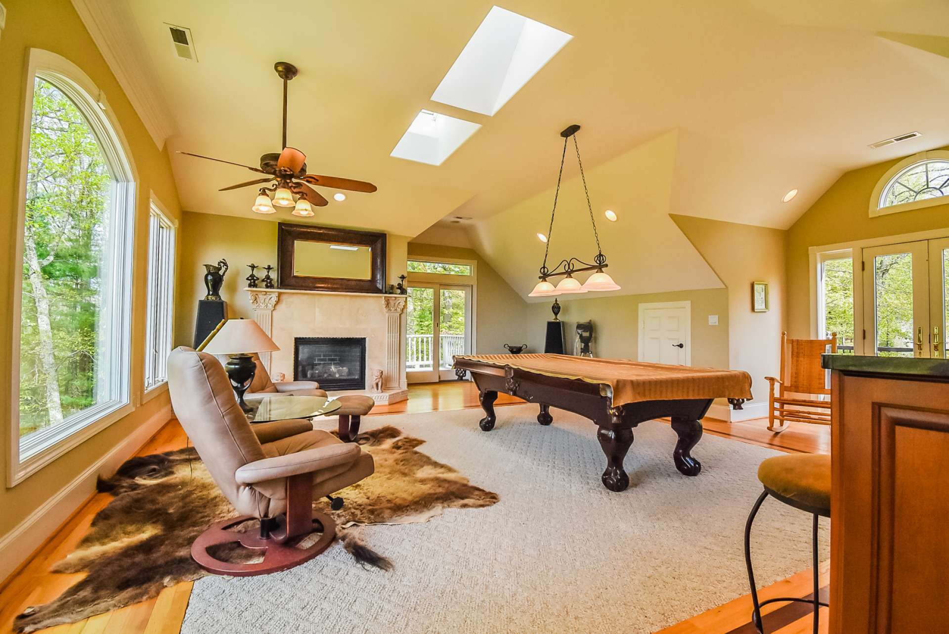 The second level features a large game room with the gas log fireplace, skylights, private deck, and full bath.