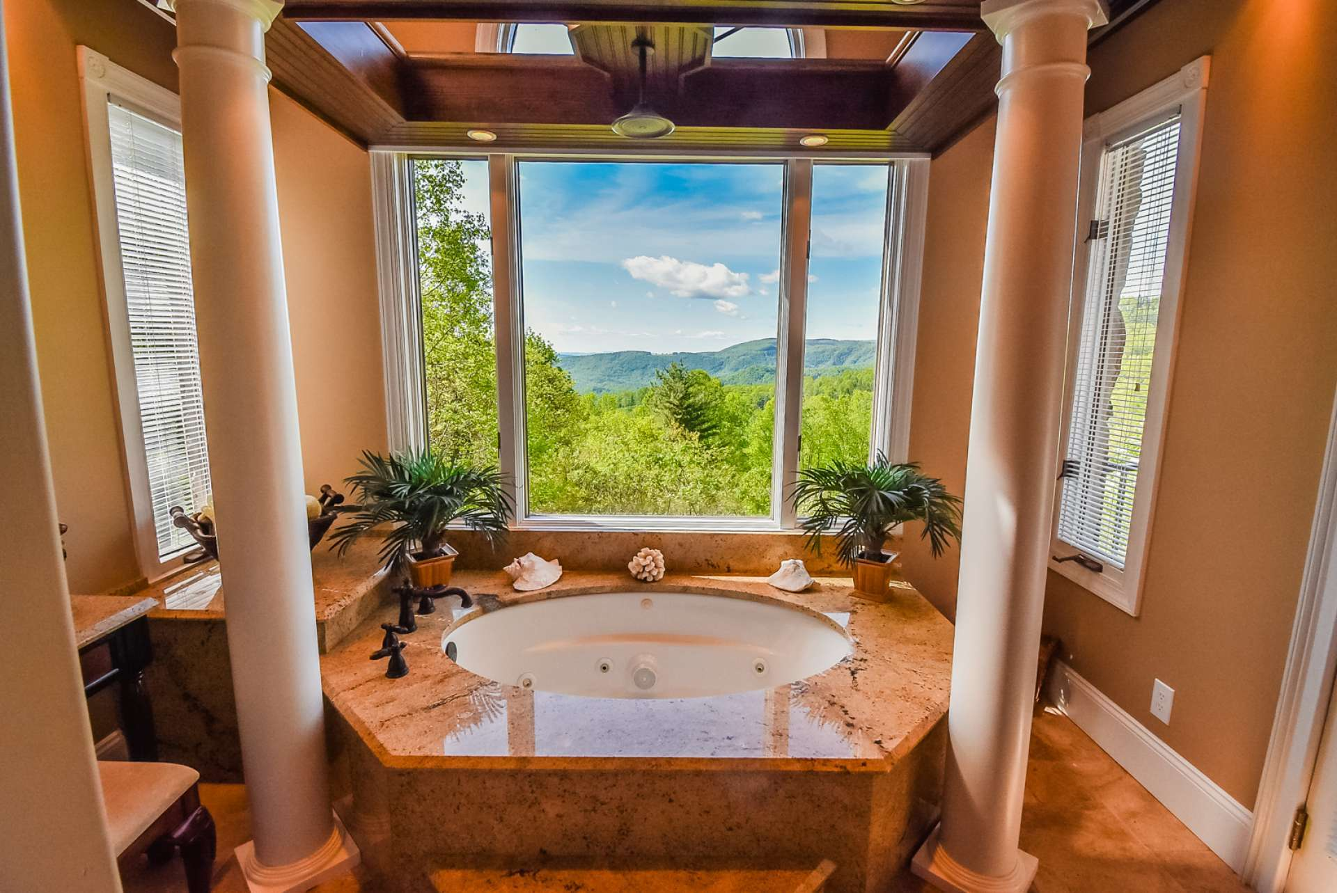This luxurious master bath provides a spa-like experience with its jetted tub with rain shower head surrounded by stunning long range mountain views.