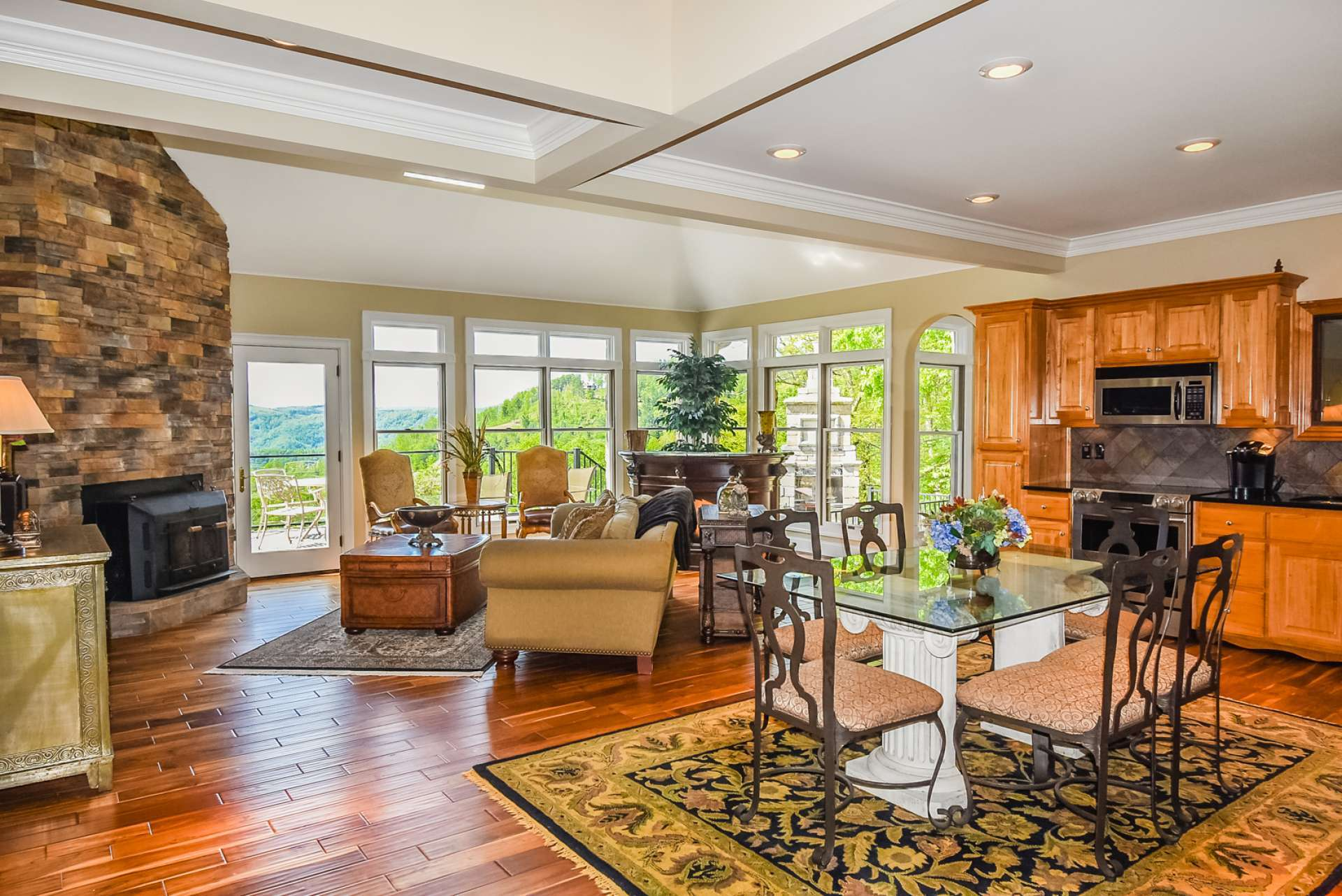 The light filled great room features Teak flooring, stone fireplace with wood stove insert, and a wall of windows to enjoy the views.