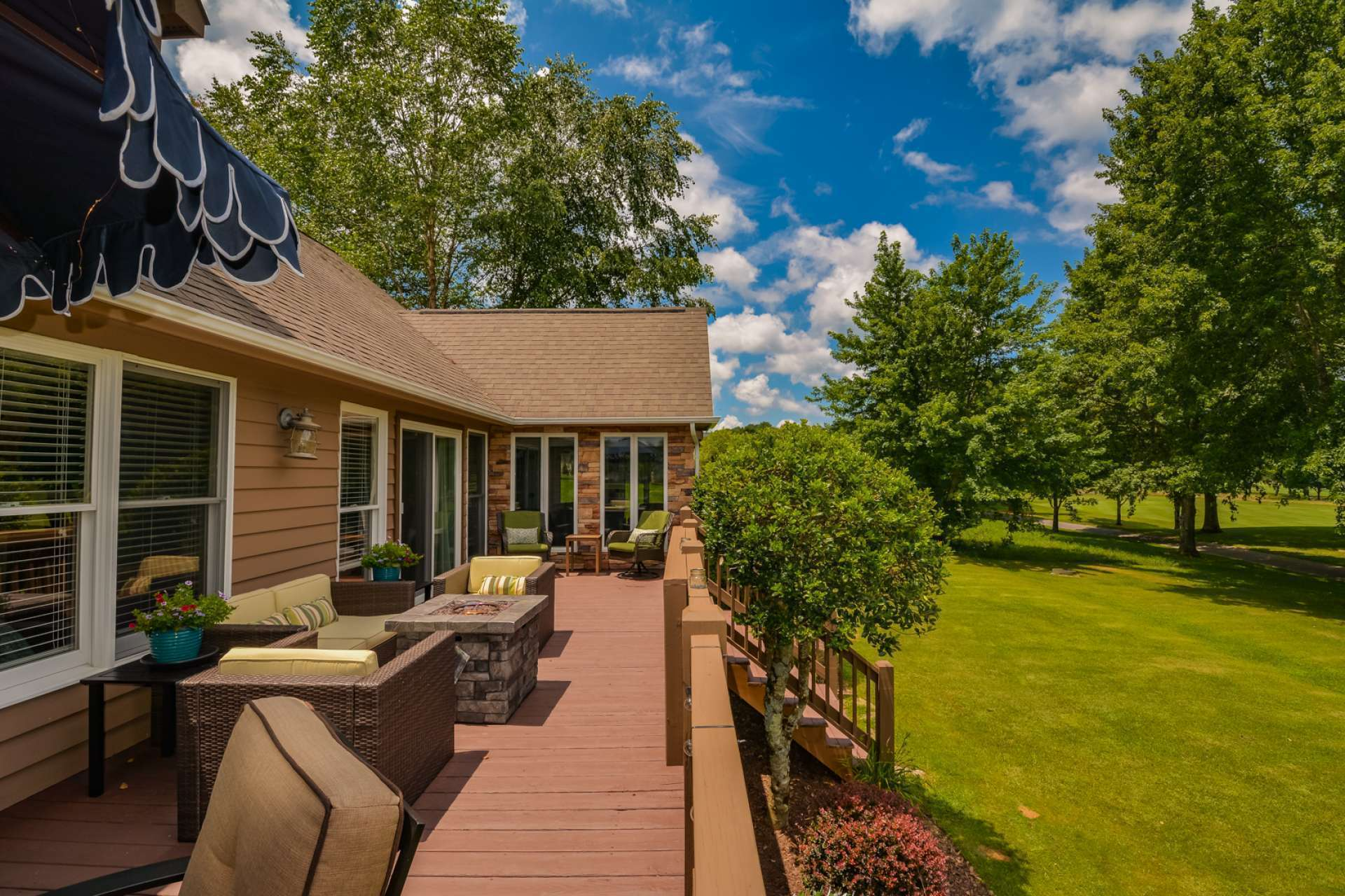 An open spacious deck overlooking lush landscaping and the pond creates an outdoor living area that is pure paradise.