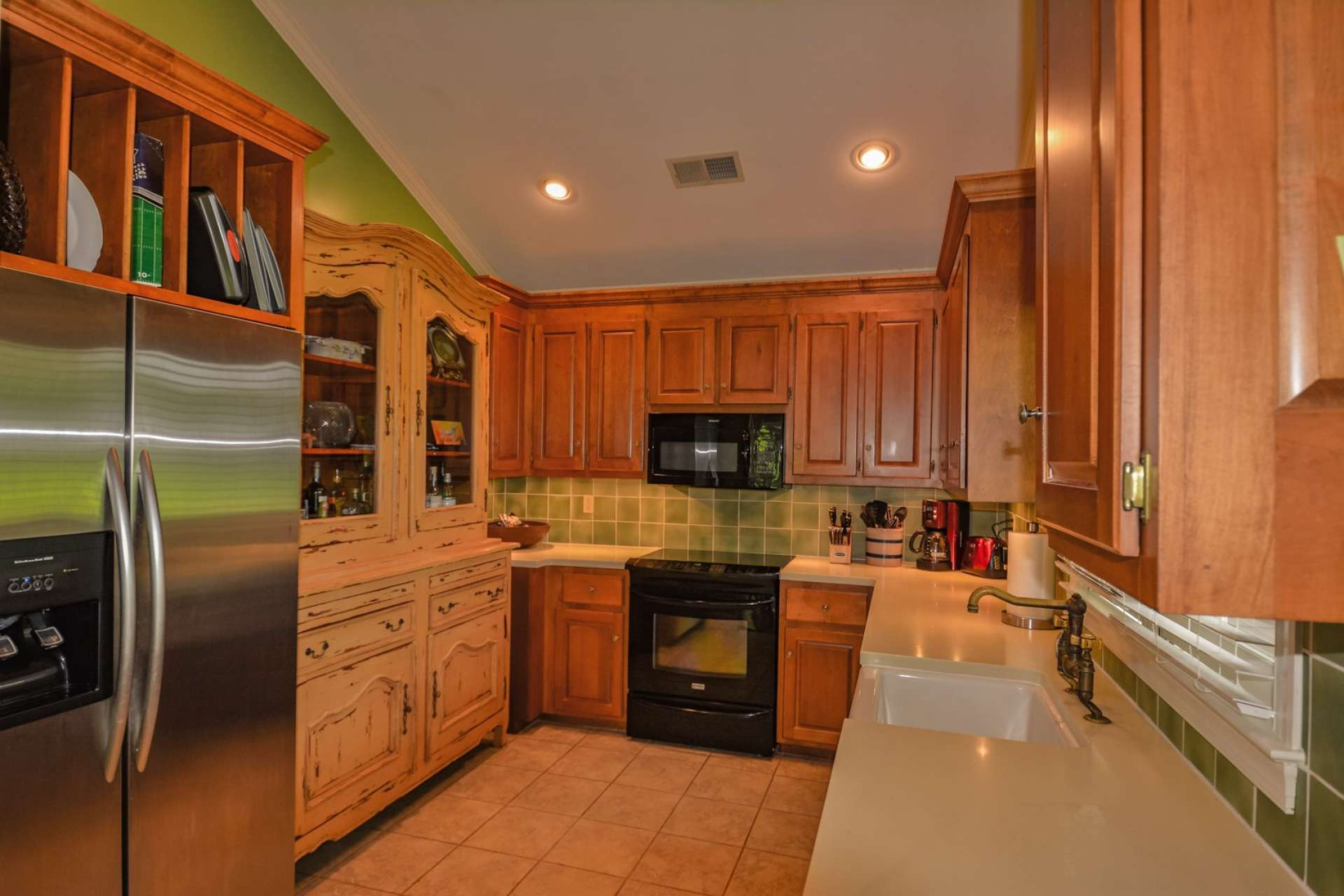 The galley style kitchen features Corian counters, tile flooring and ample cabinetry for work and storage space.