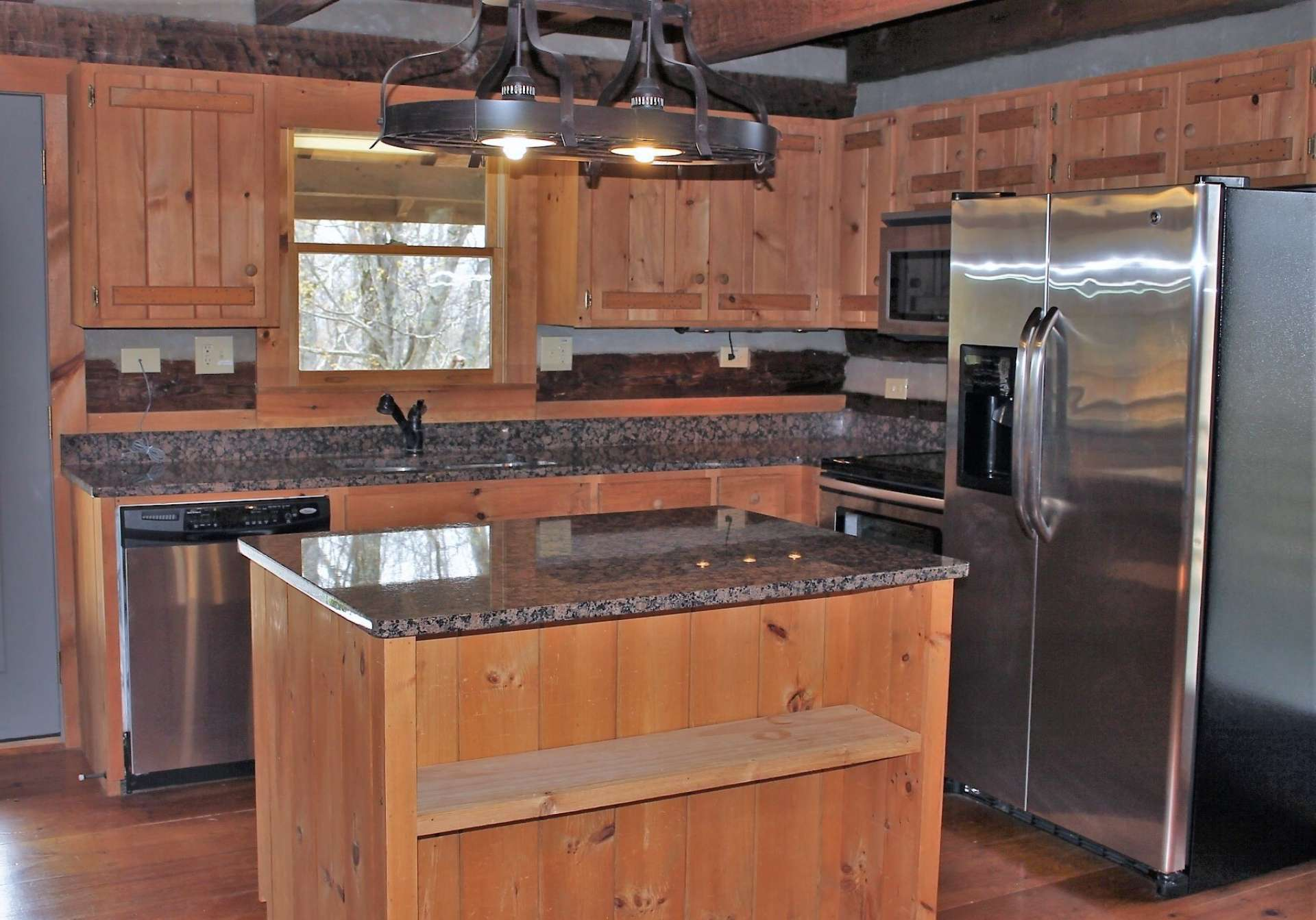 Kitchen is beautifully equipped with stainless appliances, granite counter tops, island and rustic custom cabinets.
