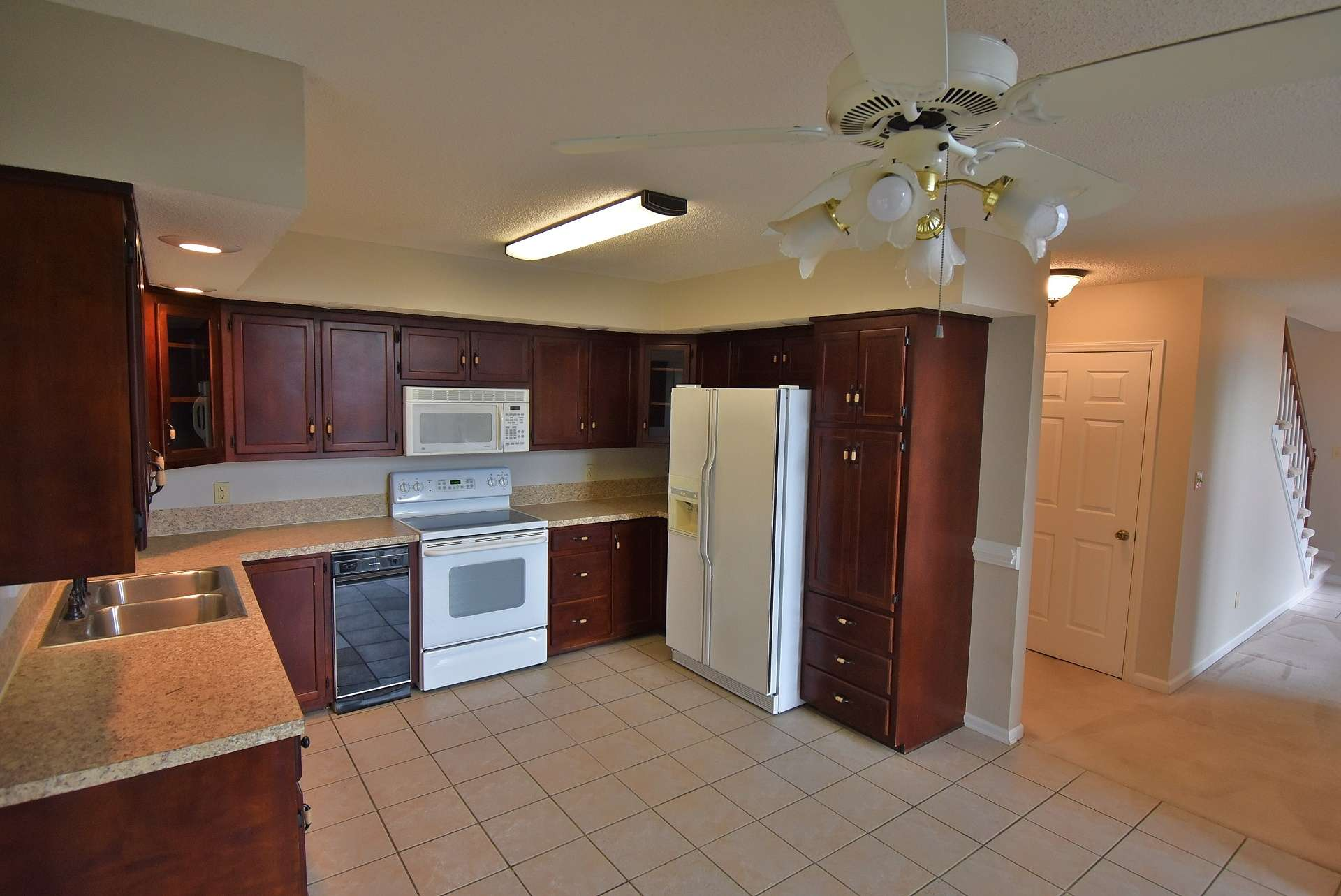 This spacious kitchen features ceramic tiled floor and offers plenty of work and storage space.