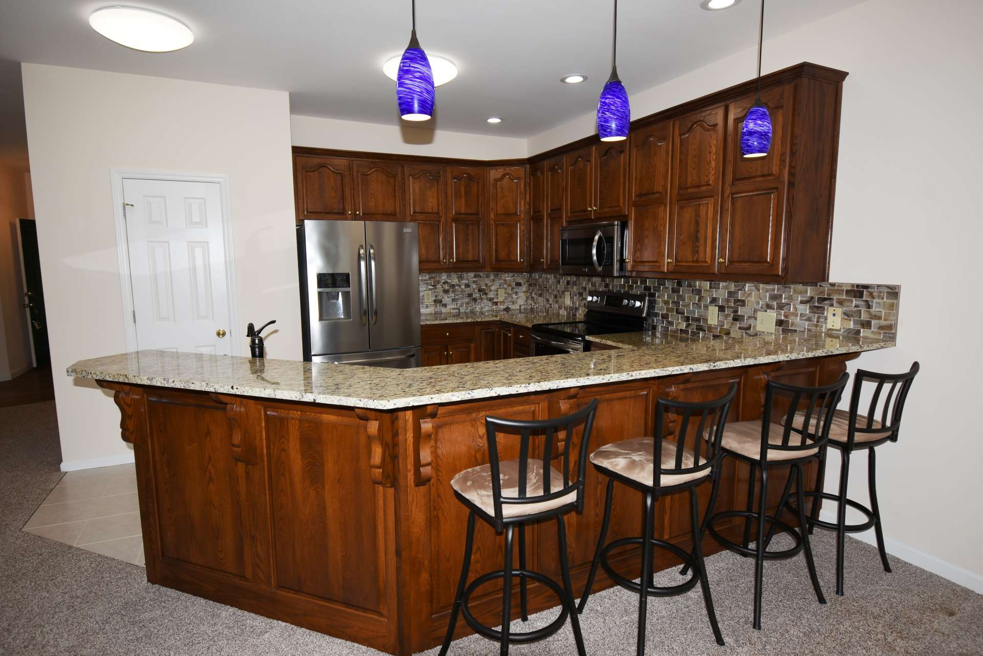 The well appointed and efficient kitchen offers stainless appliances, granite counter tops, and plenty of work and storage space including a pantry and a bar with seating.