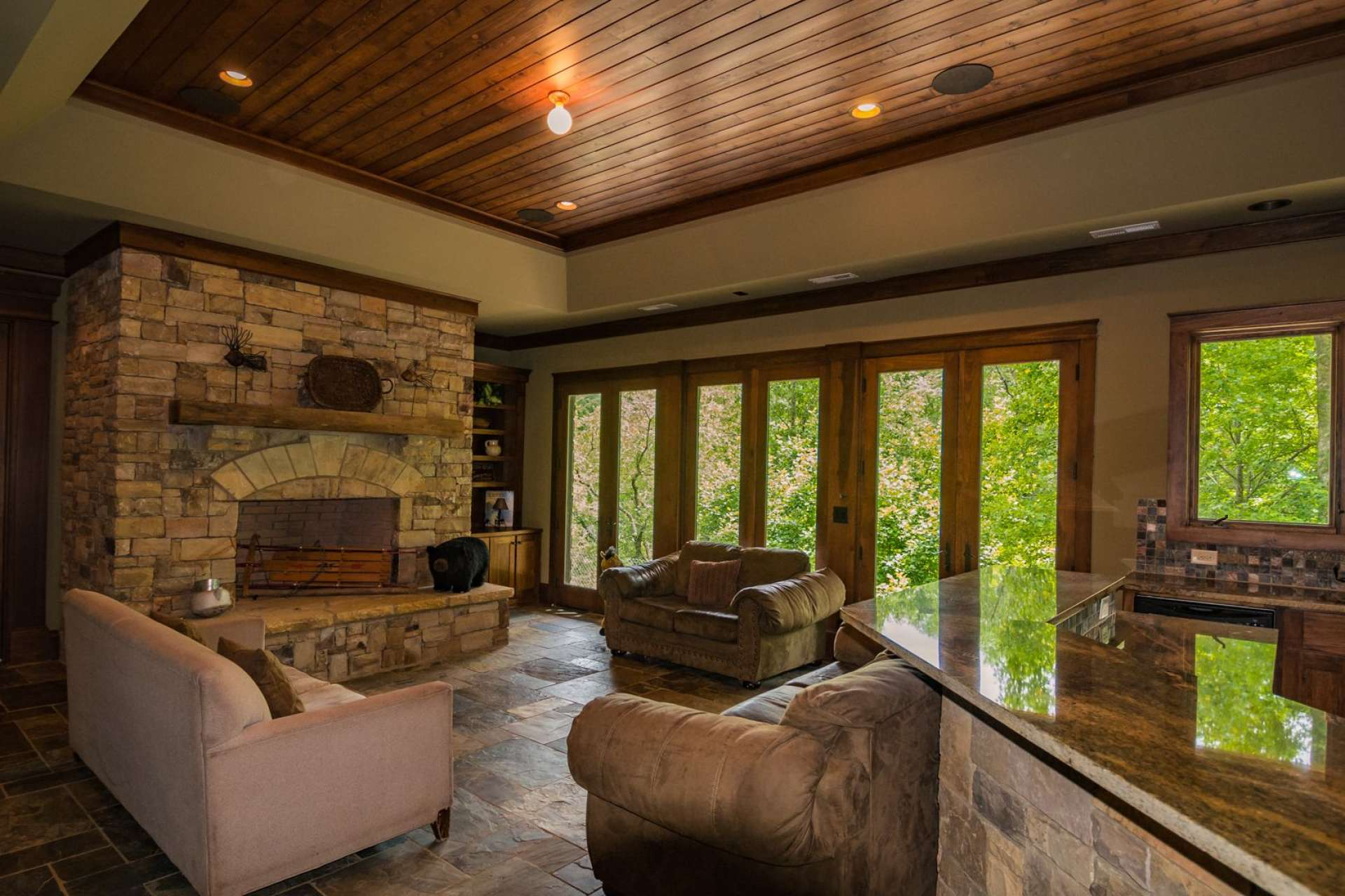 The great room is open and features high ceilings with exposed beams, tall windows to capture the outdoor scenery and natural light, beautiful wood floors, plus a stone fireplace with gas logs to warm up those cool winter evenings.