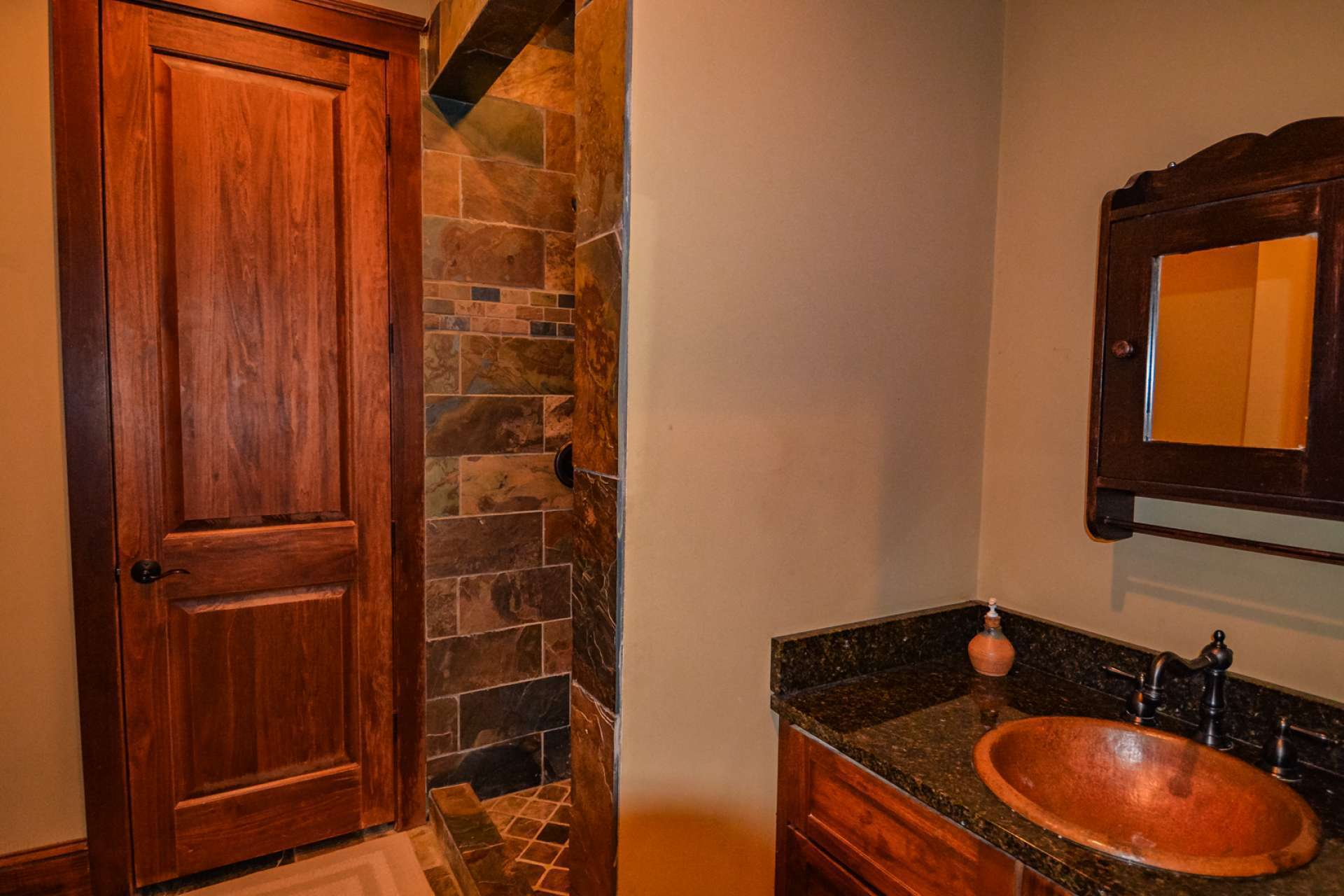 The lower level bathroom has a beautifully tiled shower and a copper sink.