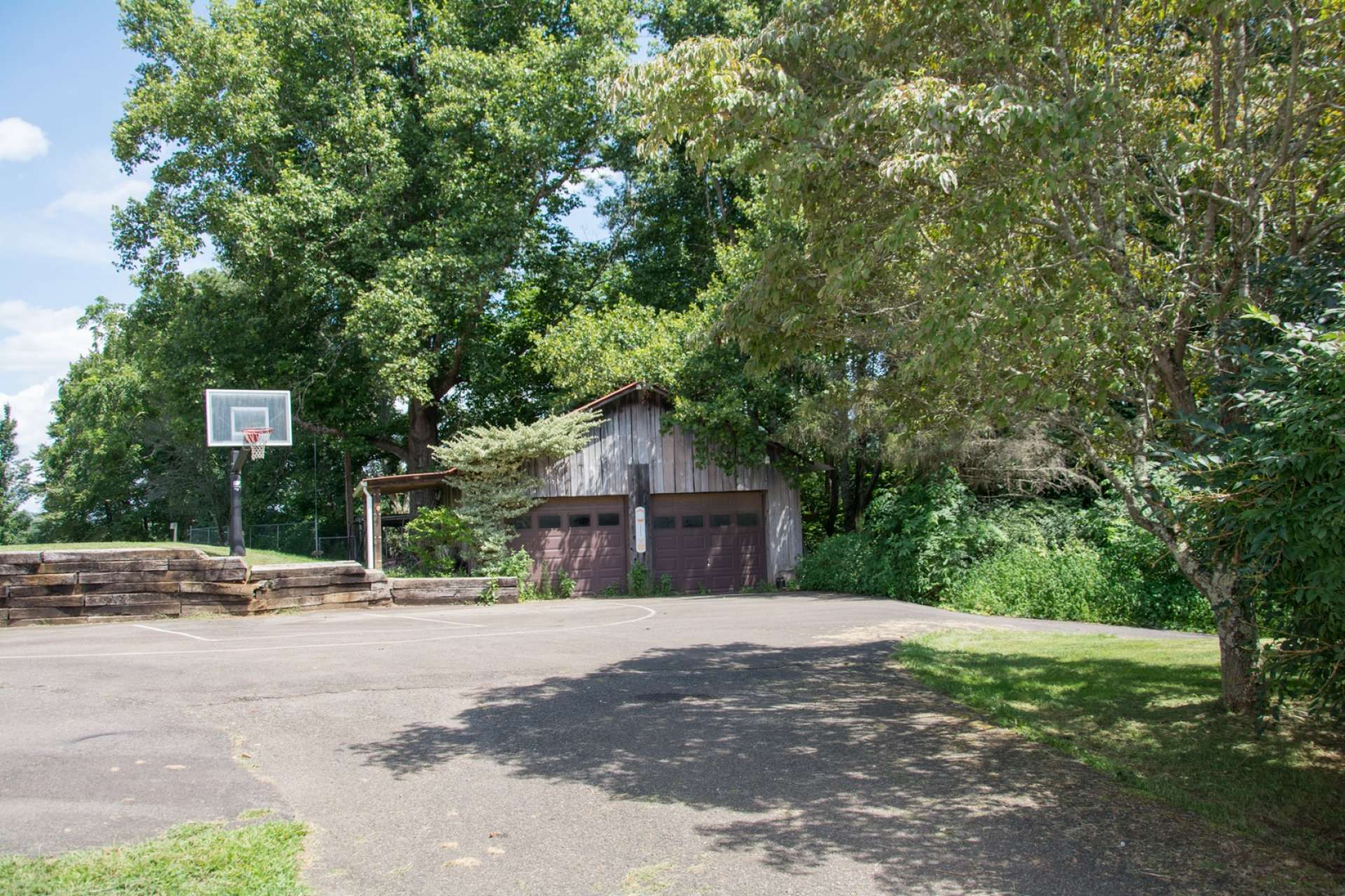 An added bonus is the detached garages, equipment shed, and this paved space that is perfect for parking or basketball.