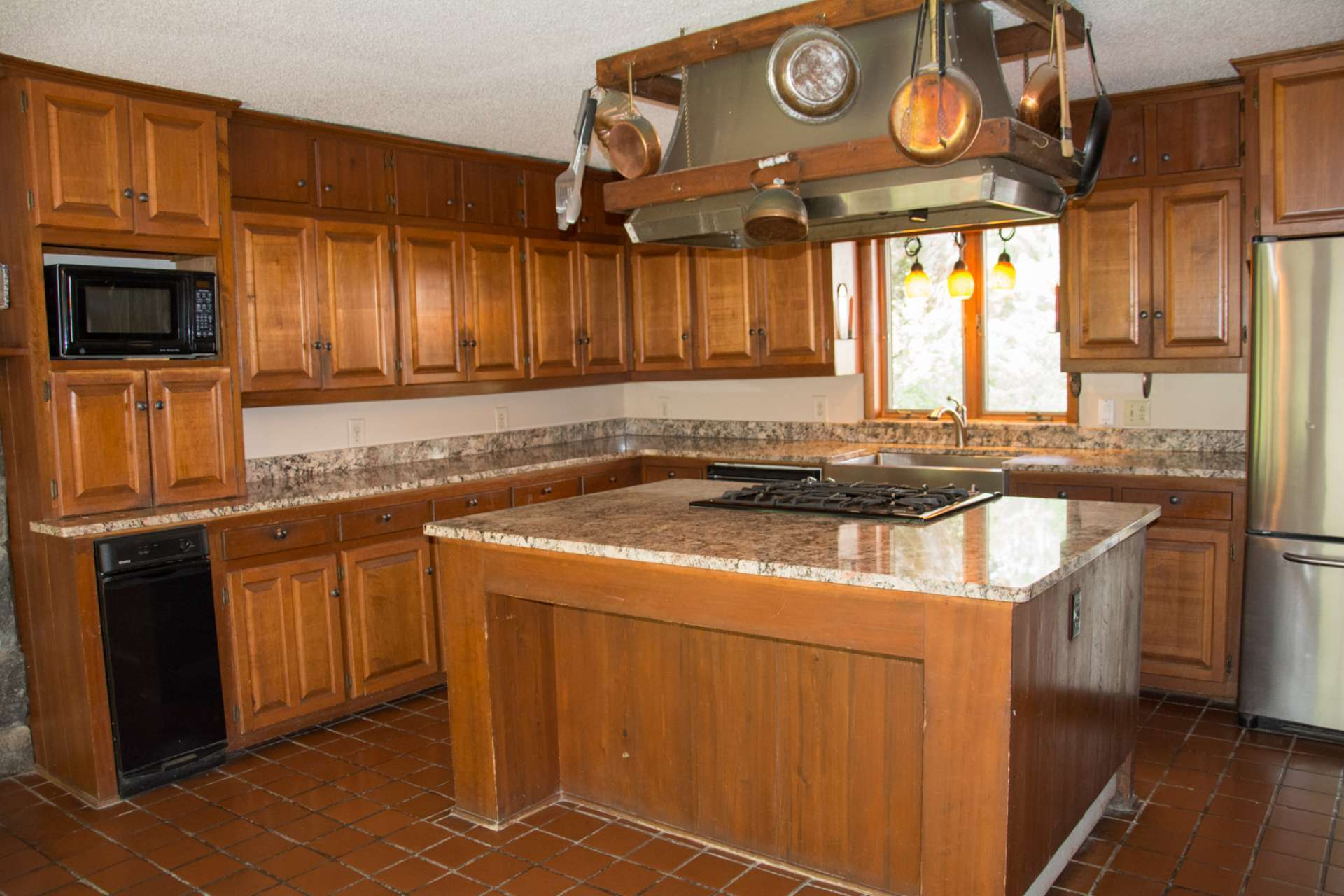 A spacious kitchen features granite counter tops, apron sink, large center island, gas range, and tiled floor.
