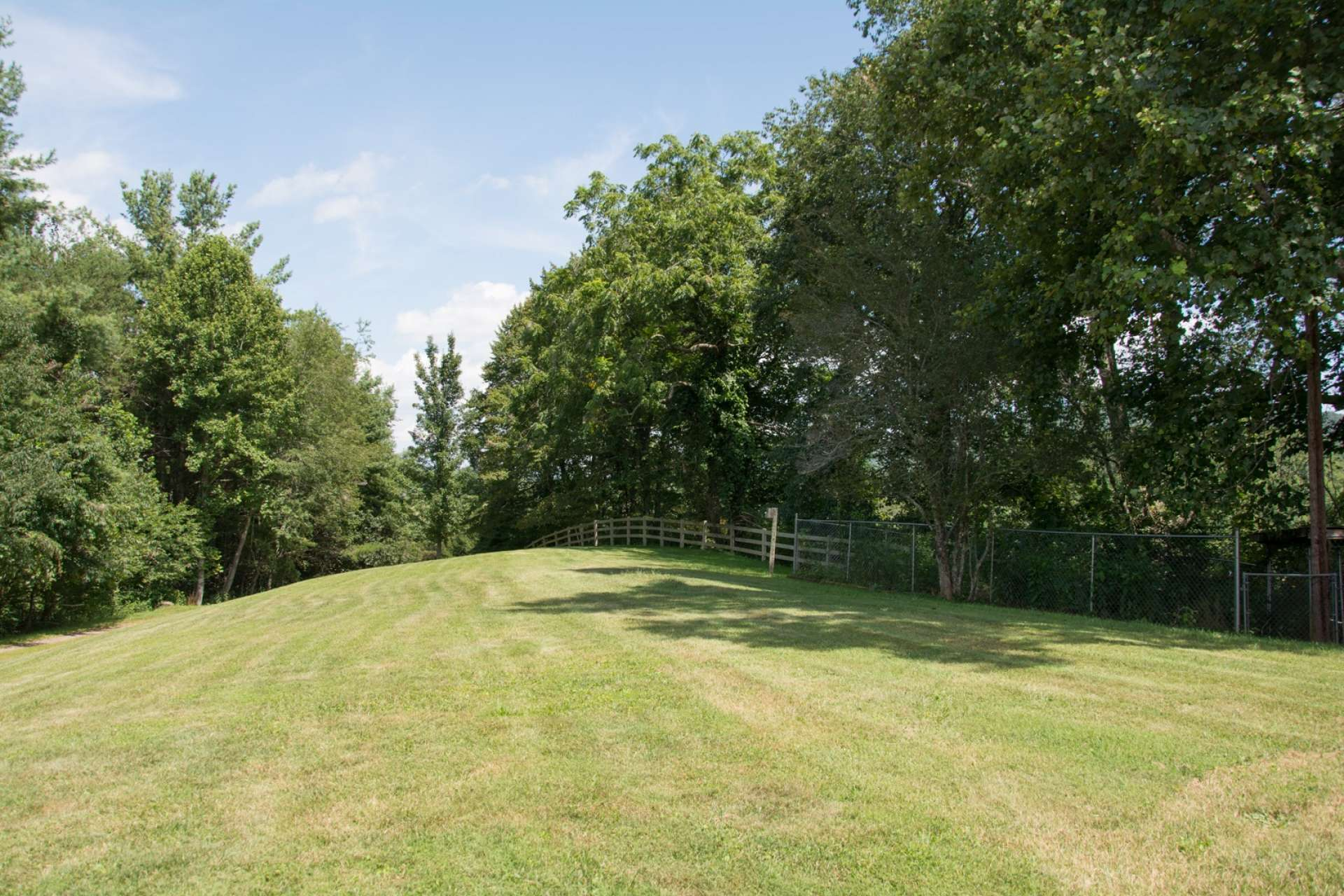 The 18 acre setting offers lots of green space for crops, gardens, play, or livestock. Serene woodlands, with a diverse mixture of native hardwoods, evergreens and beautiful mountain foliage, offer plenty of exploration and/or hunting opportunities.