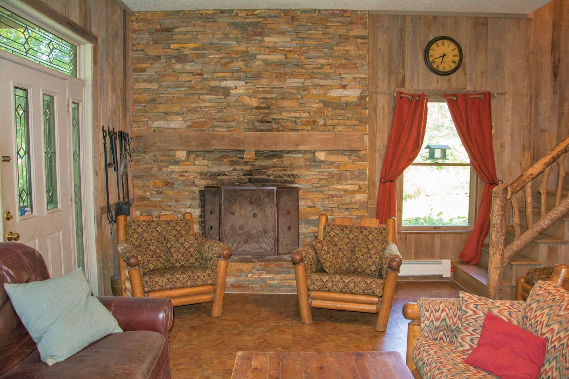 A spacious family room features barn wood accents, stone wood-burning fireplace, and a wet bar for those family gatherings.