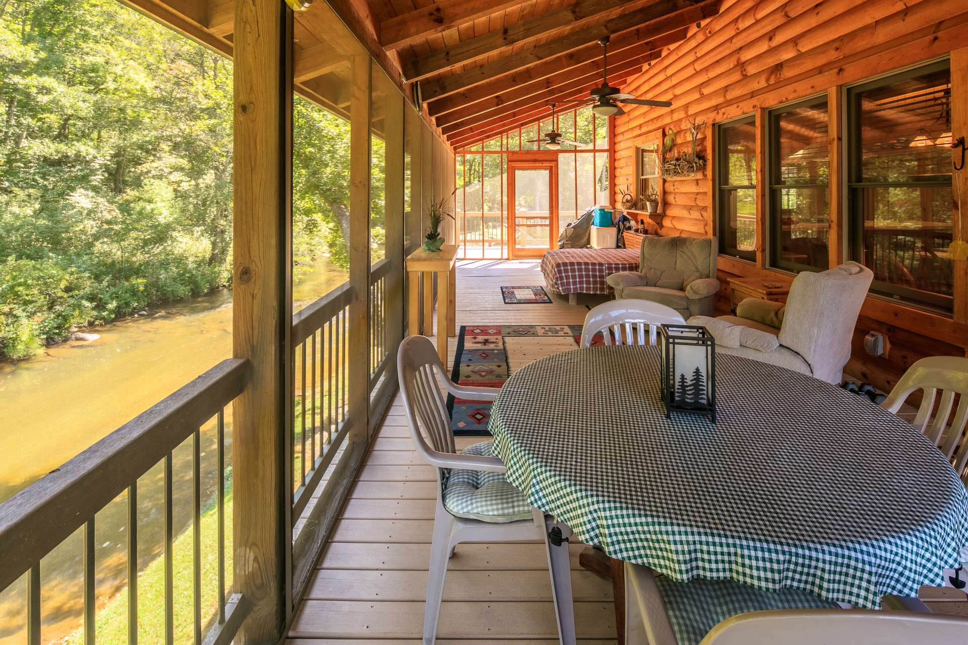 The great room also offers easy access to the back screened porch for alfresco dining above the creek.