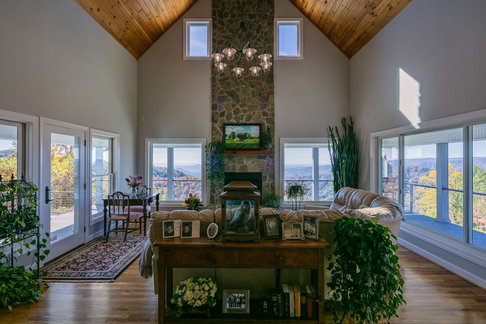 The living area features high vaulted wood ceilings, gleaming wood floors, massive floor to ceiling stone fireplace, and a wall of windows to showcase the views that include southern views into Piedmont North Carolina and western views to Grandfather Mountain, Sugar and Beech Mountains.