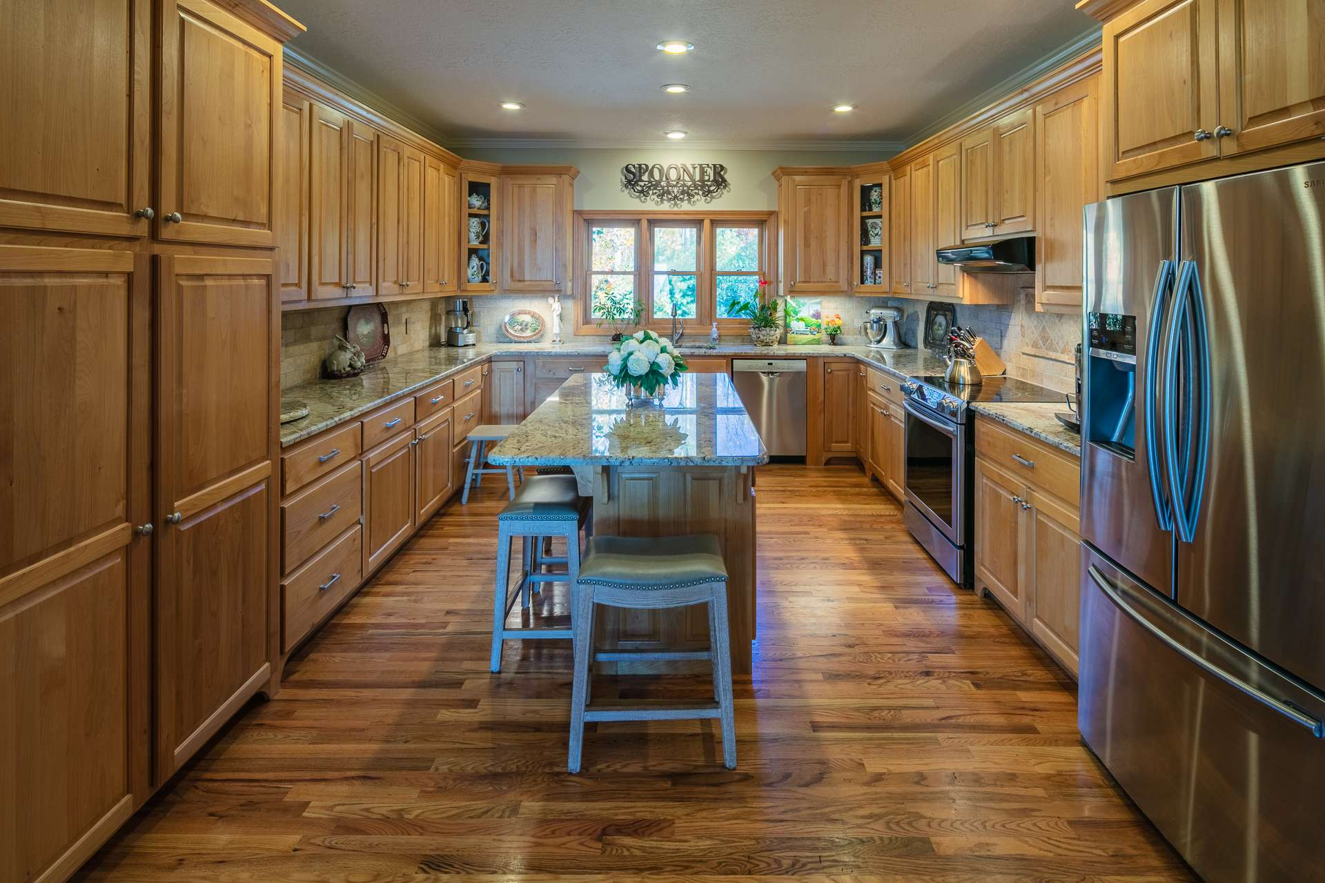 This  spacious well appointed kitchen offers custom cabinetry, granite countertops,  stainless appliances, and abundant work and storage space that includes a center island with bar seating.