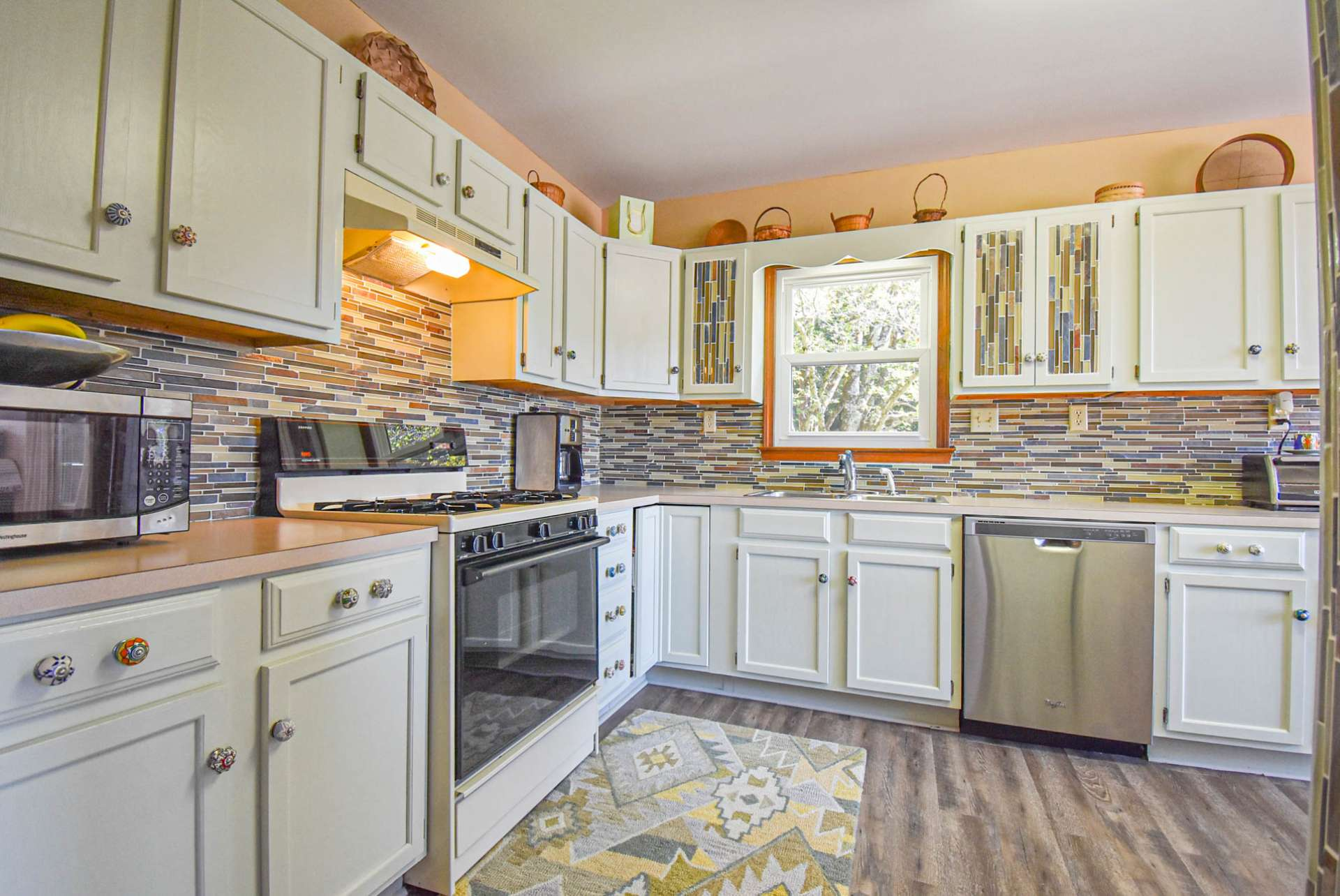 Notice the tiled accents and custom cabinetry hardware. Appliances include refrigerator, gas range, and stainless dishwasher.