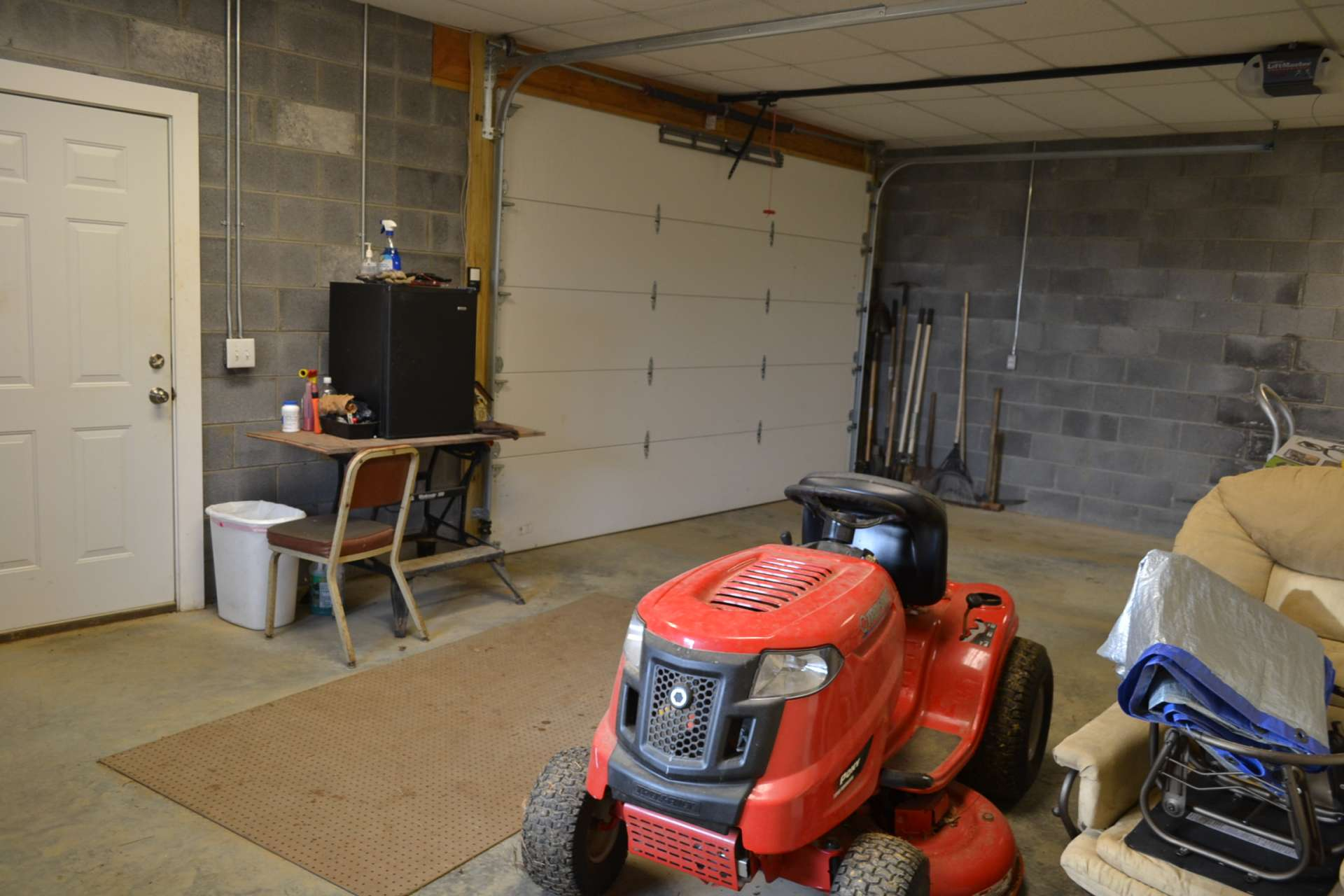 The full walkout lower level offers expansion potential on one side, and a workshop/garage area on the other side.  The garage/workshop area is plenty large enough for your vehicle and your lawn and garden equipment.