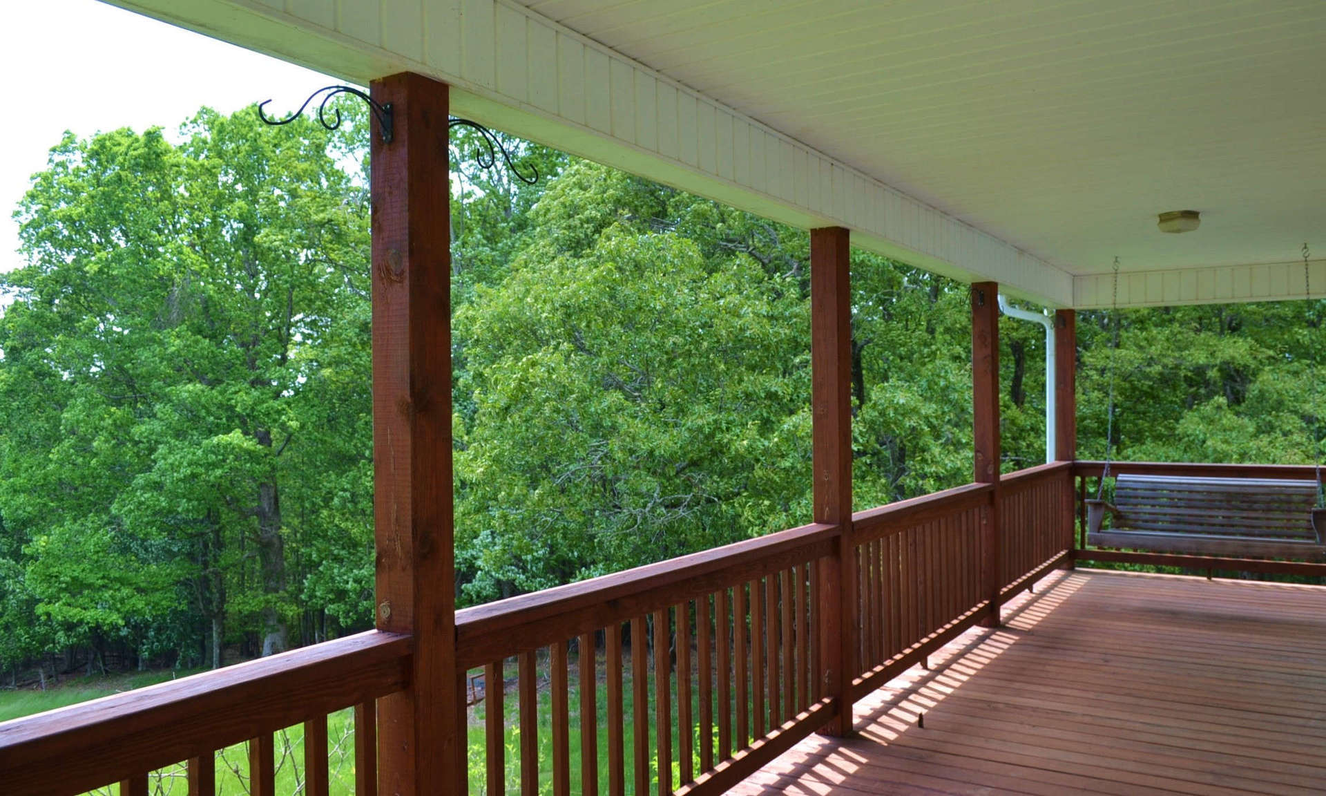 A full length covered deck is the ideal space to enjoy a tall glass of iced tea while enjoying the views, mountain scenery, and the sounds of Nature.