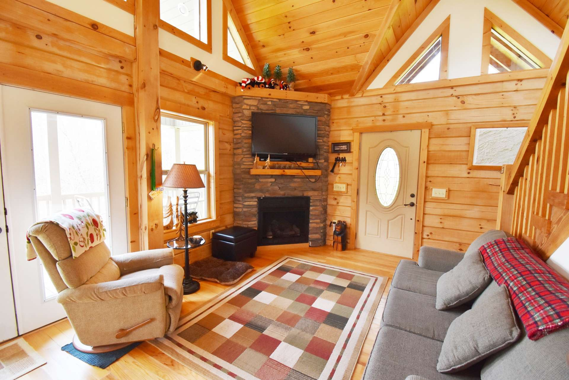 The bright and sunny vaulted great room features a wall of windows  filling the space with natural light, gleaming hardwood floors, and a stone fireplace with gas logs for added warmth and fireside romance on chilly winter evenings.