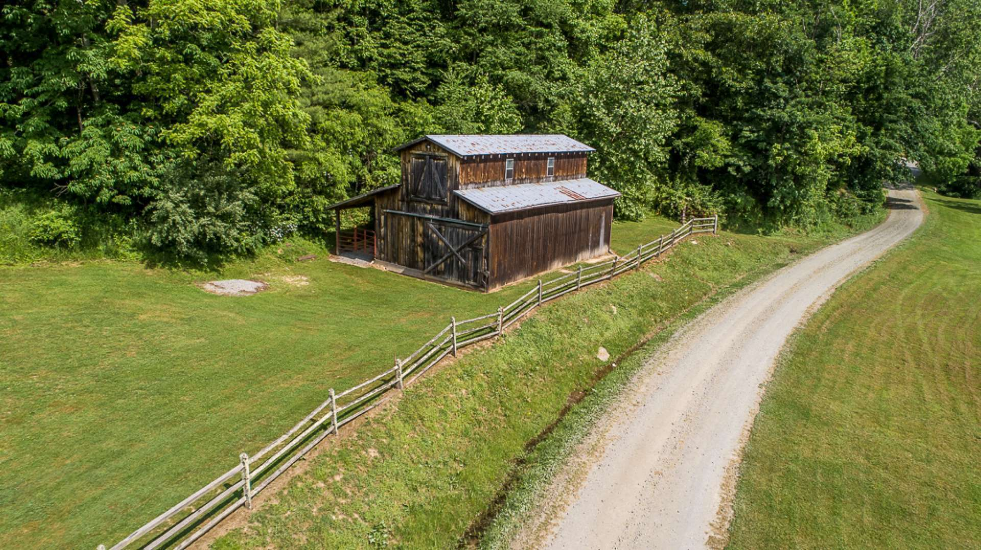This homestead style hardwood barn features two stalls and plenty of room for equipment or livestock. The wooded areas are great for exploring, too.