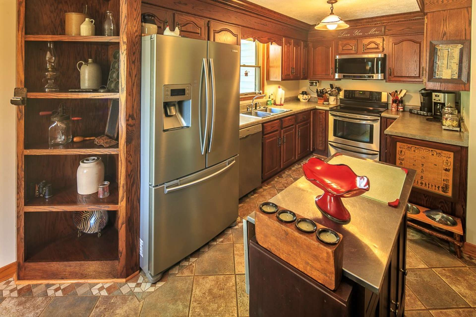 An efficient kitchen features stainless steel appliances, oak cabinetry, wood floors, and plenty of work and storage space.