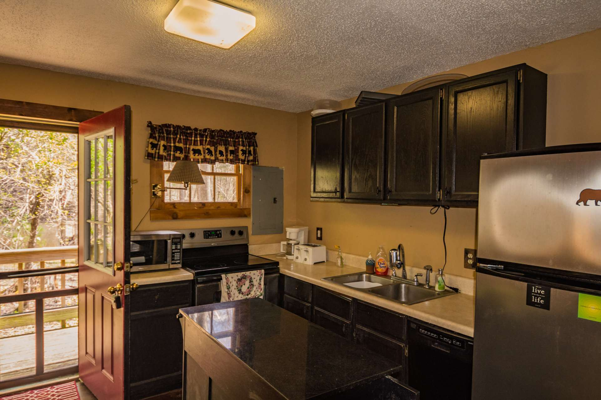 The functional step saving kitchen offers stainless appliances with ample work and storage space, and opens up to the back porch