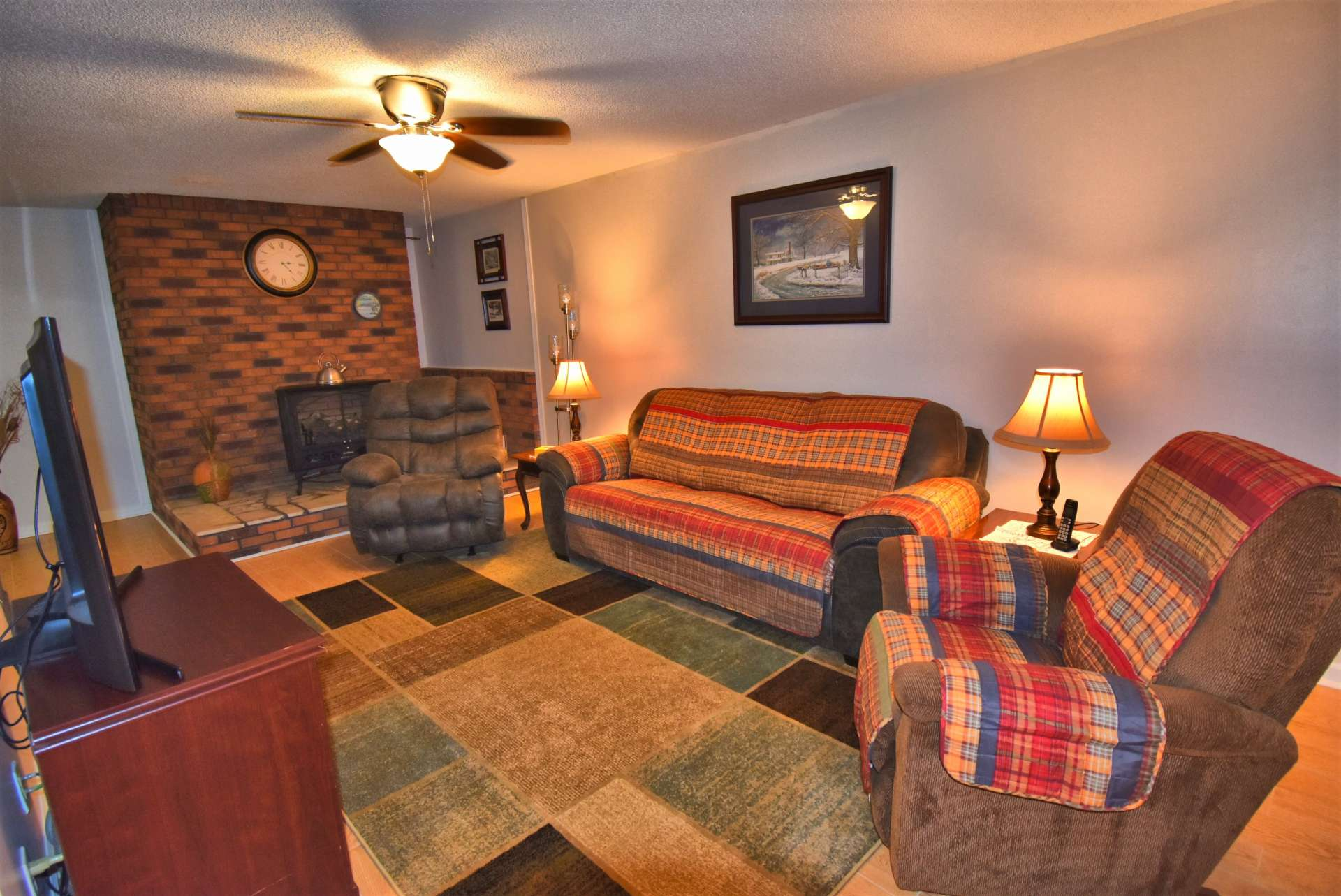 The lower level living area features new flooring and a gas log stove with the option of having a wood burning stove.